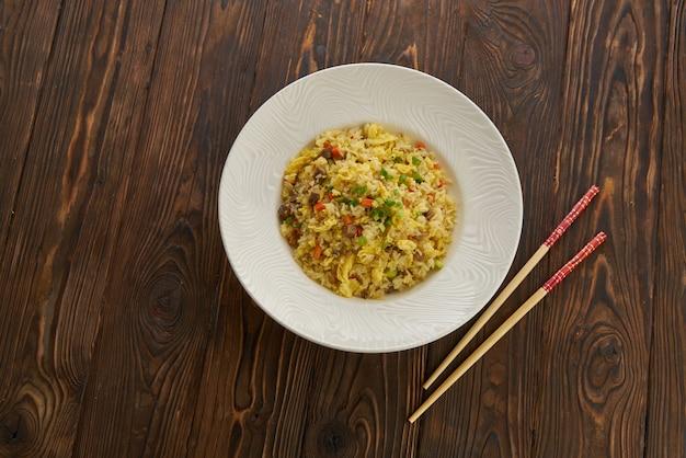 Pyszny Smażony Ryż Azjatycki Z Wołowiną, Jajkiem, Marchewką, Czosnkiem I Zieloną Cebulą Pałeczkami Poziomy Widok Z Góry Na Drewnianym Stole Biały Talerz, Miejsce Premium Zdjęcia