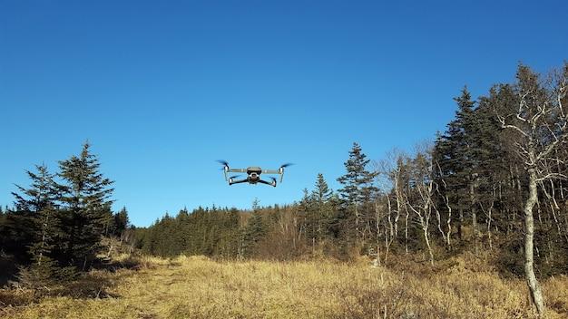 Quadkopter Leci Po Błękitnym Niebie Na Terenach Górskich. Uav. Nowoczesna Technologia . Premium Zdjęcia