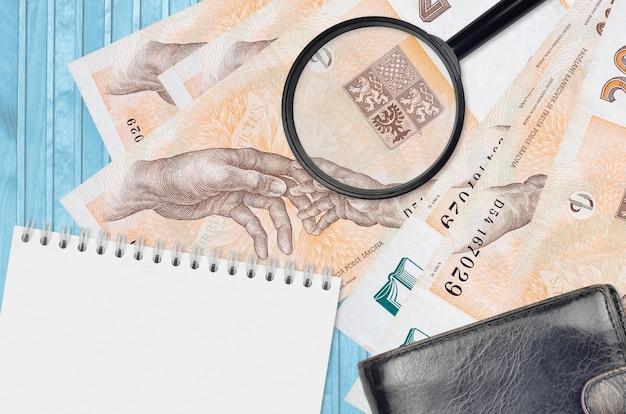 Rachunki 200 Koron Czeskich I Szkło Powiększające, Czarna Torebka I Notatnik. Pojęcie Fałszywych Pieniędzy. Wyszukaj Różnice W Szczegółach Dotyczących Rachunków Pieniężnych, Aby Wykryć Fałszywe Pieniądze Premium Zdjęcia