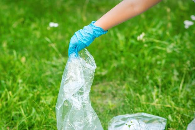 Rączka Dziecka Czyści Park Z Plastikowych śmieci Leżących Na Zielonej Trawie Premium Zdjęcia