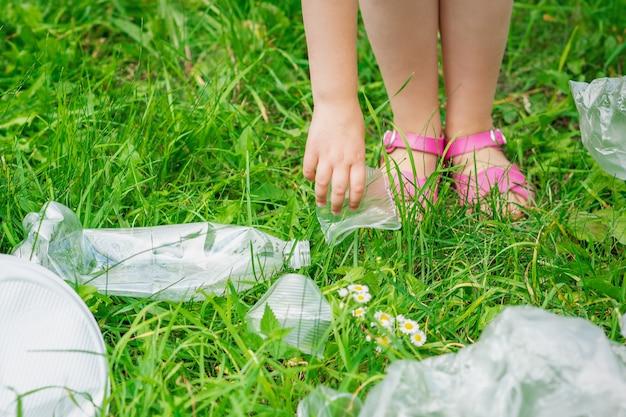 Rączka Dziecka Czyści Zieloną Trawę Z Plastikowych śmieci W Parku Premium Zdjęcia
