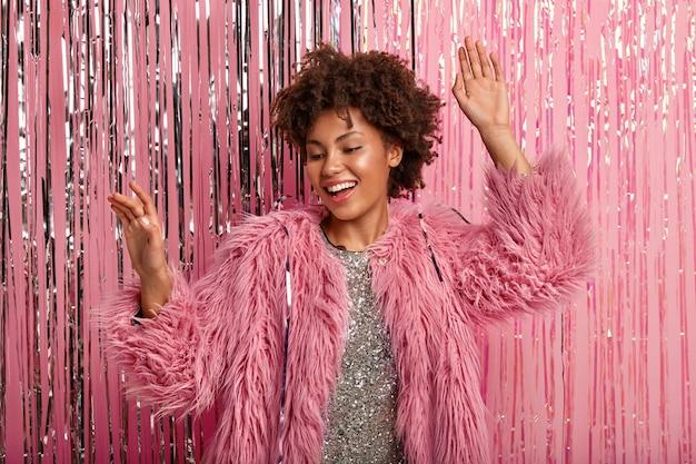 Radosna Afroamerykanka Szczerze Się śmieje, Czuje Się Zrelaksowana, Tańczy Przy Ulubionej Muzyce, Nosi Różowe Futro I Błyszczącą Sukienkę, Modelki Na Różowej ścianie. Uroczystość Darmowe Zdjęcia