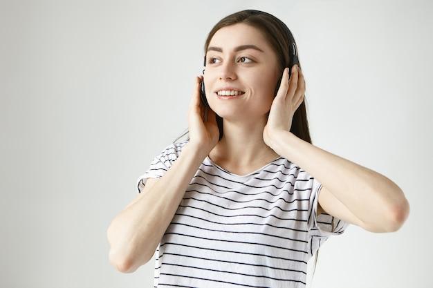 Radosna, Beztroska Młoda Ciemnowłosa Kobieta Dwudziestokilkuletnia Relaksująca Się W Domu, Ubrana W Zwykłe Ubrania I Bezprzewodowe Słuchawki Darmowe Zdjęcia