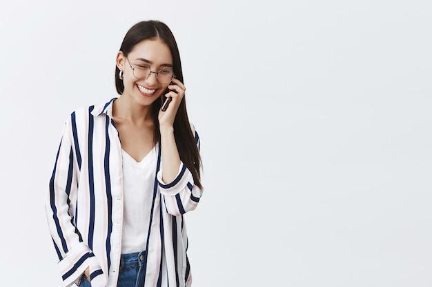 Radosna I Odnosząca Sukcesy Młoda Kobieta Moda Rozmawia Przez Telefon, Ciesząc Się Rozmową. Beztroska Zrelaksowana Kobieta W Bluzce W Paski I Okularach, Patrząc W Dół Z Uroczym Uśmiechem, Trzymając Smartfon Darmowe Zdjęcia