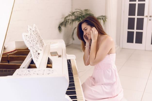 Radosna Kobieta W Różowej Sukience Słuchanie Muzyki W Słuchawkach Telefonu Siedzi Przy Fortepianie Premium Zdjęcia