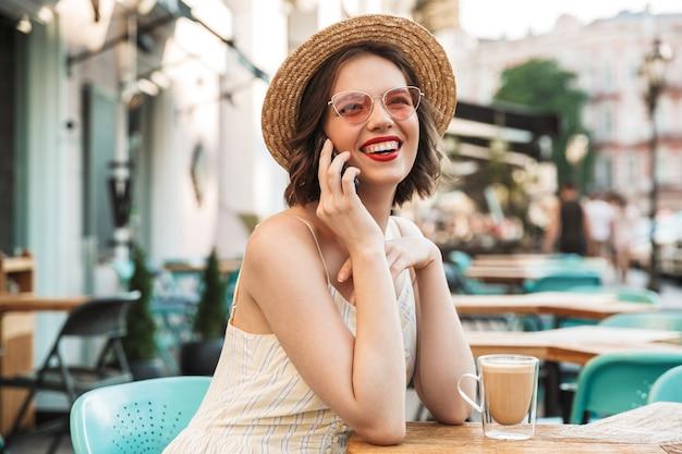 Radosna Kobieta W Sukni I Słomkowym Kapeluszu Rozmawia Przez Smartfona Premium Zdjęcia