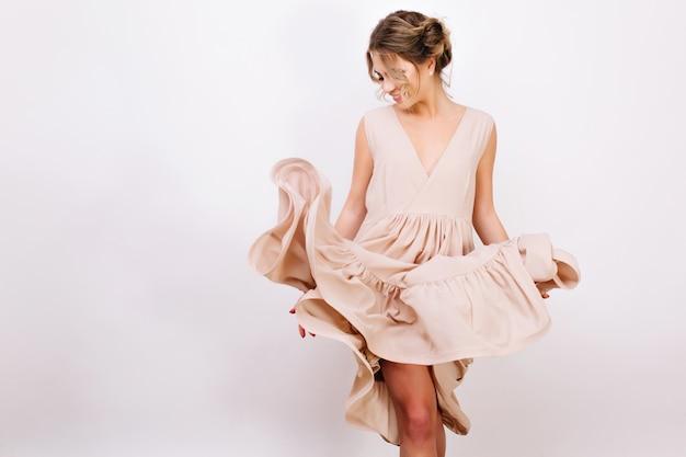 Radosna Kręcona Dziewczyna Z Uroczą Fryzurą Pozuje Figlarnie Podczas Przymierzania Nowej Stylowej Sukienki. Szczupła Młoda Kobieta W Modny Strój Vintage Taniec, Na Białym Tle. Darmowe Zdjęcia