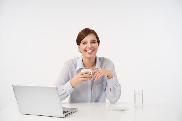 Radosna Młoda Brązowowłosa Kobieta Z Przypadkową Fryzurą, śmiejąca Się Radośnie Podczas Picia Kawy W Dzień Pracy, Ubrana W Niebieską Koszulę, Pozując Na Białym Darmowe Zdjęcia