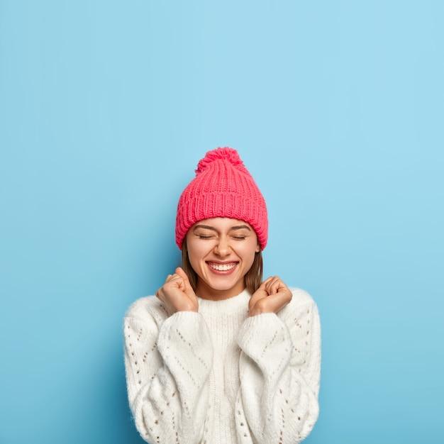 Radosna Młoda Dziewczyna Czuje Się Uszczęśliwiona, Unosi Zaciśnięte Pięści, Będąc W Dobrym Nastroju, Nosi Biały Sweter I Różową Czapkę, Ubrana W Ciepłe Ubrania W Zimny Jesienny Dzień, Odizolowana Na Niebieskiej ścianie Darmowe Zdjęcia