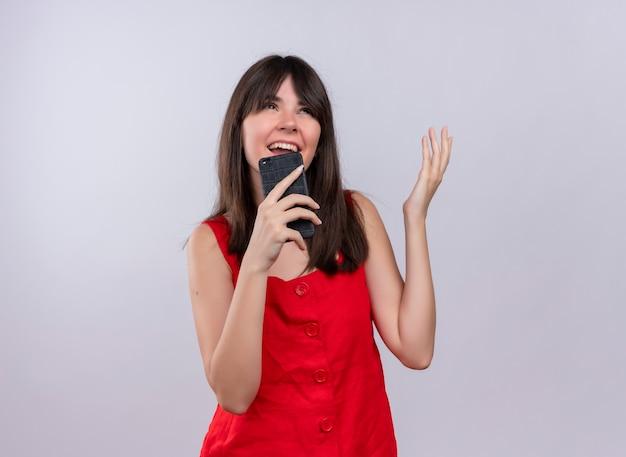 Radosna Młoda Dziewczyna Kaukaski Trzymając Telefon I Podnosząc Rękę Patrząc Na Kamery Na Na Białym Tle Z Miejsca Na Kopię Darmowe Zdjęcia