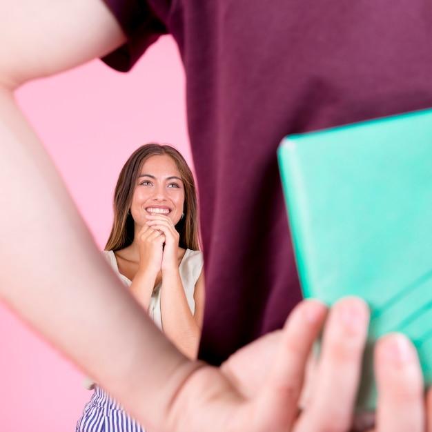 Radosna młoda kobieta patrzeje mężczyzna chuje prezent w ręce Darmowe Zdjęcia