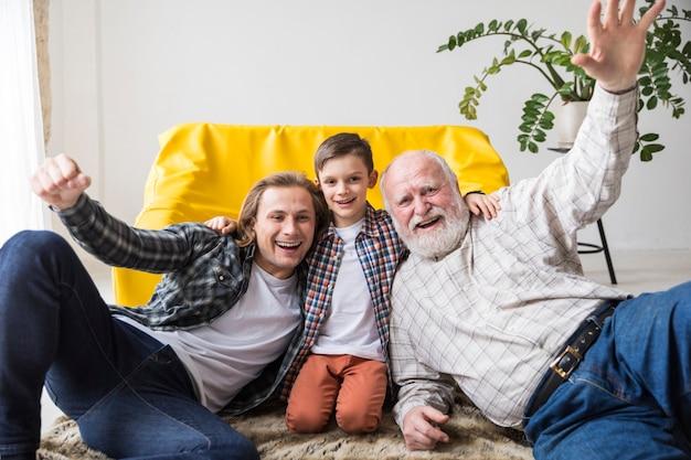Radosna wielopokoleniowa rodzina siedząca razem na dywanie Darmowe Zdjęcia