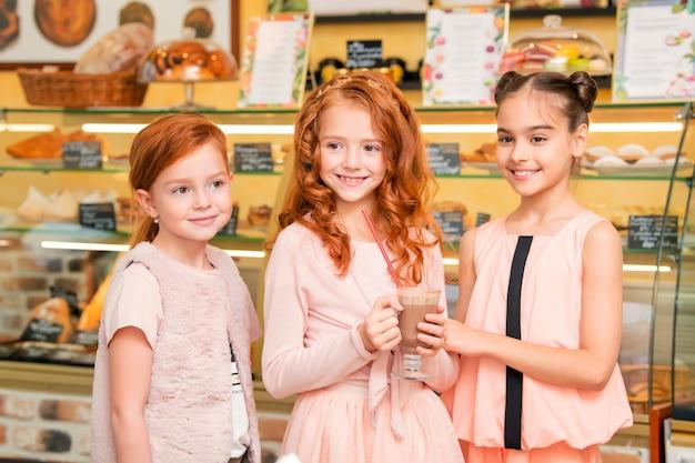 Radosne Dzieci Stoją W Kawiarni Premium Zdjęcia