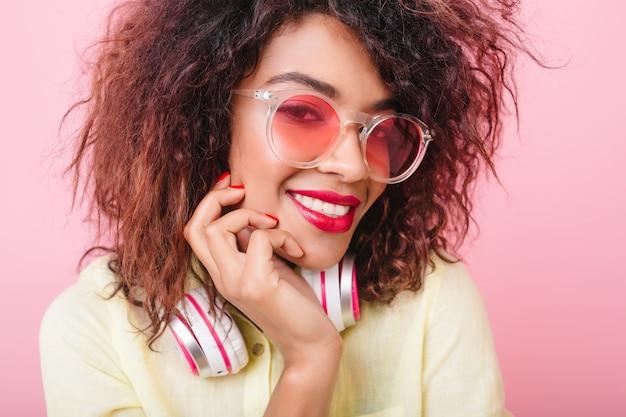 Radosny Afrykański Modelka Z Czerwonymi Ustami, Uśmiechając Się, Dotykając Jej Twarzy. Close-up Portret Uroczej Kręconej Pani W Okularach Przeciwsłonecznych I Słuchawkach, śmiejąc Się Z Przyjemności. Darmowe Zdjęcia