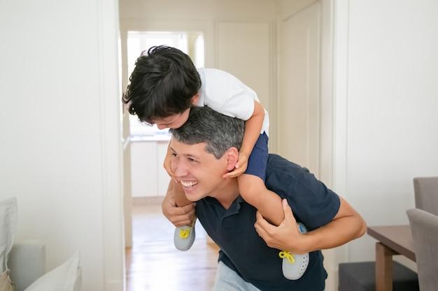 Radosny Mały Chłopiec Siedzi Na Ramionach Ojca I Się śmieje. Darmowe Zdjęcia