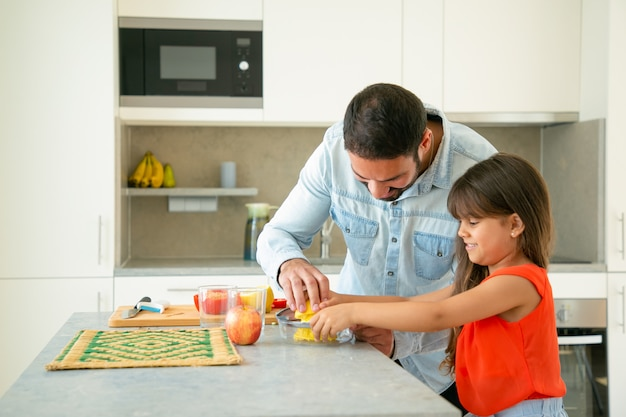 Radosny Młody Tata I Córka Wspólnie Gotują. Dziewczyna I Jej Ojciec Wyciskają Sok Z Cytryny Na Kuchennym Blacie. Koncepcja Gotowania Rodziny Darmowe Zdjęcia