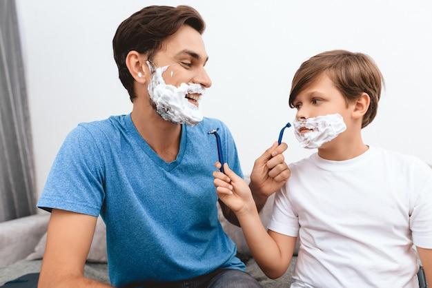 Radosny ojciec i syn z pianką na twarzach golą się. Premium Zdjęcia