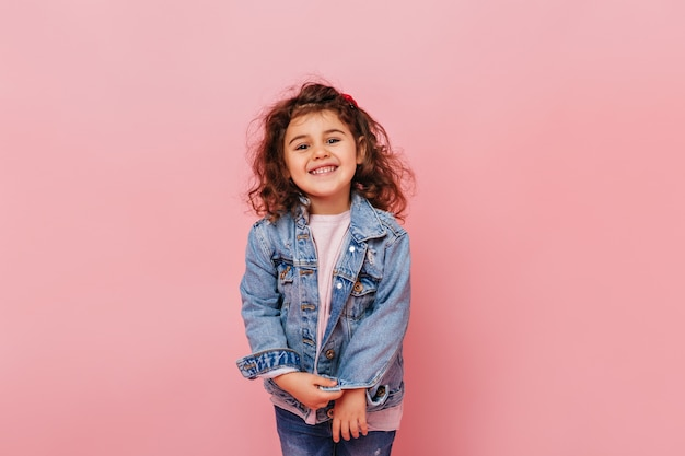 Radosny Preteen Dzieciak Z Kręconymi Włosami śmiejąc Się Z Kamery. Studio Strzał Beztroski Dziewczynka Na Białym Tle Na Różowym Tle. Darmowe Zdjęcia