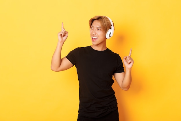 Radosny Przystojny Azjata O Blond Włosach, śpiewający I Tańczący Do Słuchania Muzyki W Słuchawkach Bezprzewodowych, Stojący Na żółtej ścianie Darmowe Zdjęcia