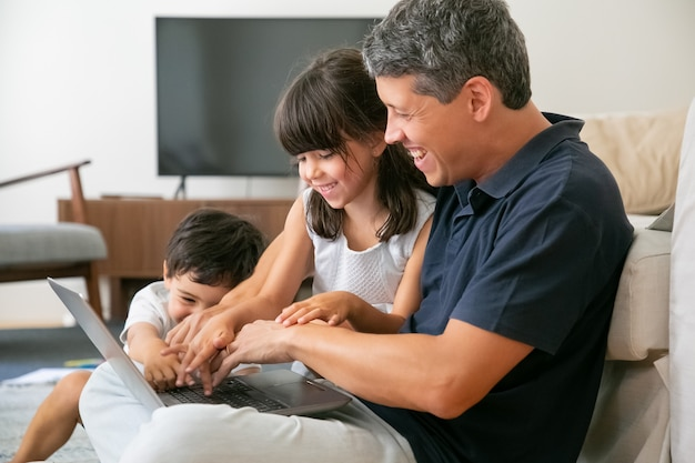 Radosny Szczęśliwy Tata I Dwoje Dzieci Razem Korzystających Z Laptopa, Siedząc Na Podłodze W Mieszkaniu, Naciskając Przyciski Na Klawiaturach. Darmowe Zdjęcia