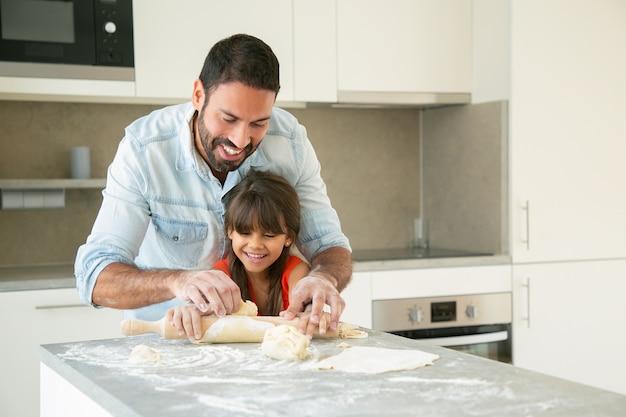 Radosny Szczęśliwy Tata I Jego Dziewczyna Spędzają Razem Czas Podczas Wałowania I Wyrabiania Ciasta W Kuchni. Darmowe Zdjęcia