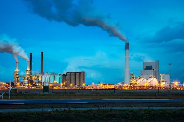 Rafineria ropy naftowej przemysł przy nocą w rotterdam, holandie. dym zanieczyszczeń z przemysłu rafinerii ropy naftowej. Premium Zdjęcia