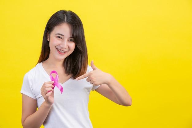 Rak piersi, kobieta w białej koszulce z satynową różową wstążką na piersi, symbol świadomości raka piersi Darmowe Zdjęcia