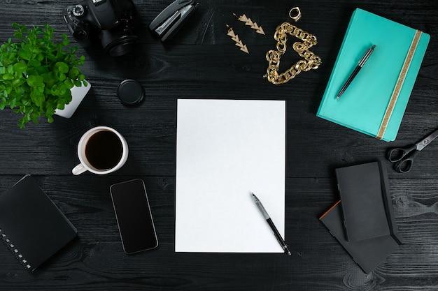 Rama Biurka Na Biurko Z Widokiem Z Góry Na Płasko. Obszar Roboczy Z Czystą Kartką Papieru, Pamiętnikiem Mięty I Urządzeniem Mobilnym Na Ciemnym Tle. Premium Zdjęcia