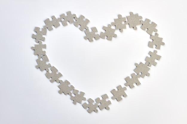 Rama Serce Wykonana Z Puzzli. Kształt Serca Z Puzzli Na Białym Tle. Szczęśliwych Walentynek. Premium Zdjęcia