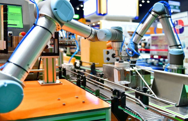 Ramię robota ustawiło szklaną butelkę z wodą na automatycznym sprzęcie maszynowym w fabryce linii produkcyjnej Premium Zdjęcia