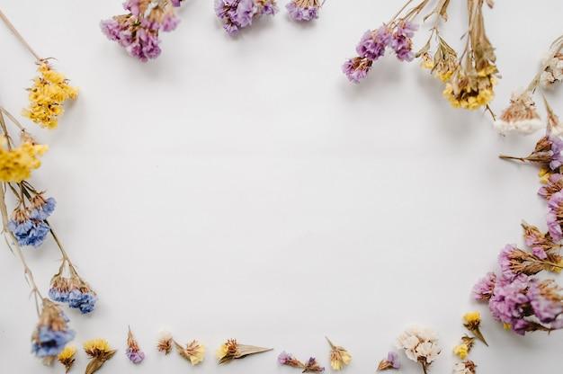 Ramka Wykonana Z Suszonych Kolorowych Kwiatów Na Białej Powierzchni Premium Zdjęcia