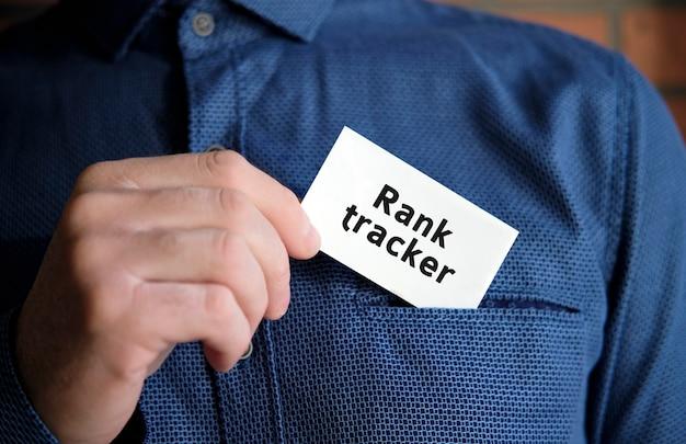 Ranga Tracker Tekst Na Białym Znaku W Dłoni Mężczyzny W Koszuli Premium Zdjęcia