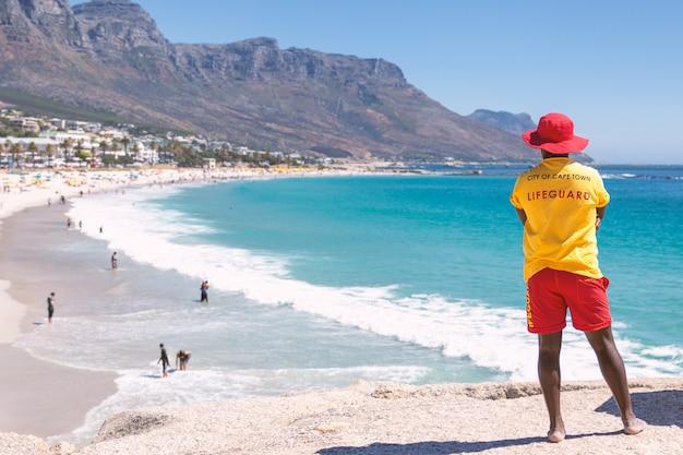 Ratownik Z Kapsztadu Ogląda Słynną Plażę Camps Bay Z Turkusową Wodą Premium Zdjęcia