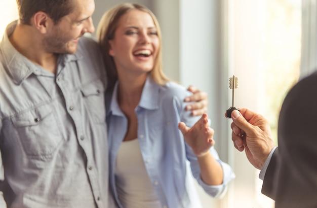 Realtor w klasycznym garniturze daje klucz do nowego mieszkania. Premium Zdjęcia