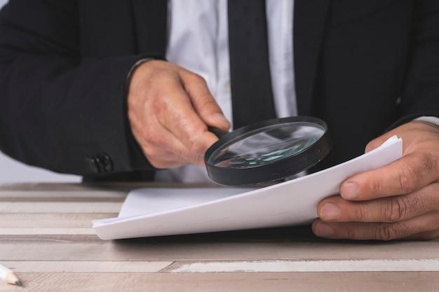 Ręce biznesmena patrząc przez szkło powiększające do dokumentów Premium Zdjęcia