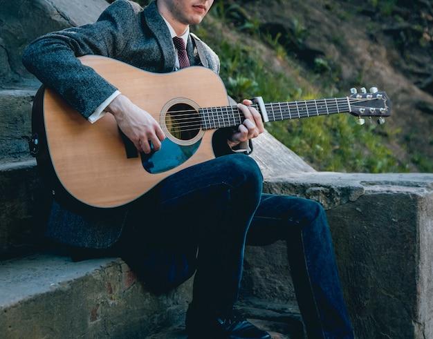 Ręce Człowieka, Gra Na Gitarze Akustycznej. Autentyczne Tło. Premium Zdjęcia