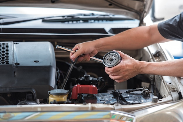 Ręce człowieka, trzymając klucz nasadki filtra oleju i filtr oleju samochodowego przygotowuje się do zmiany. Premium Zdjęcia