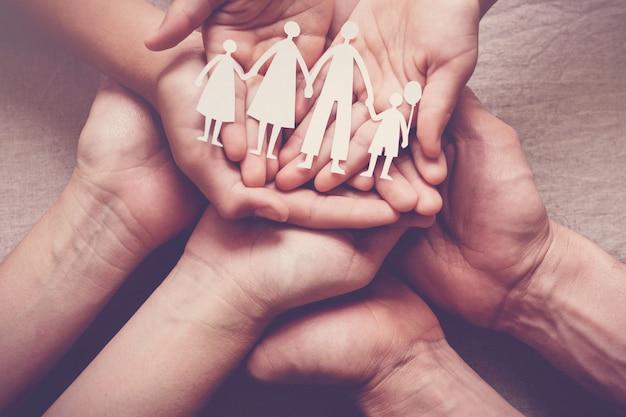 Ręce dorosłych i dzieci trzymające wycinankę z rodziny papieru, dom rodzinny, Premium Zdjęcia