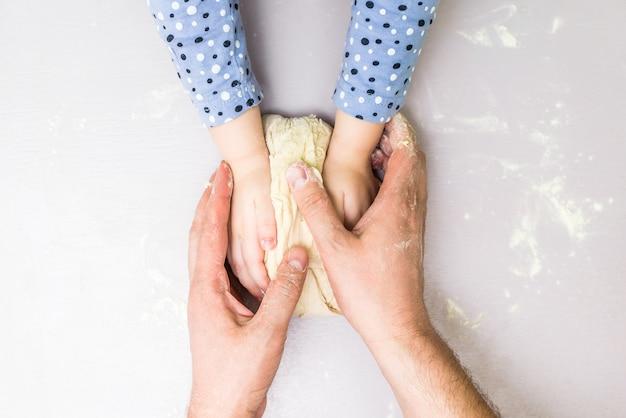 Ręce dzieci i taty tworzą ciasto Premium Zdjęcia
