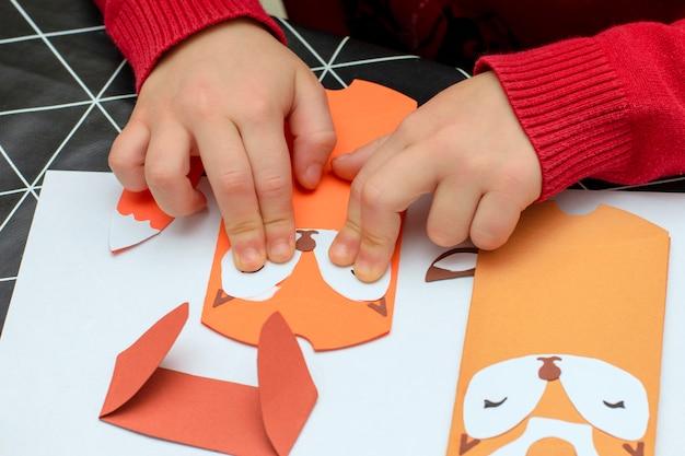 Ręce dzieci robią świąteczne wyroby papierowe Premium Zdjęcia