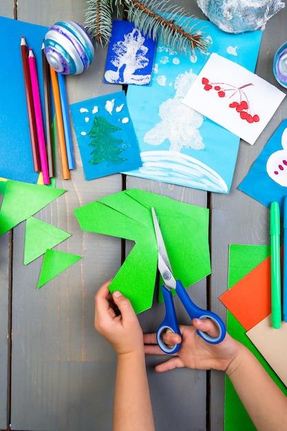 Ręce dziecka wykonują ręcznie robione świąteczne zabawki z tektury. diy dla dzieci. Premium Zdjęcia