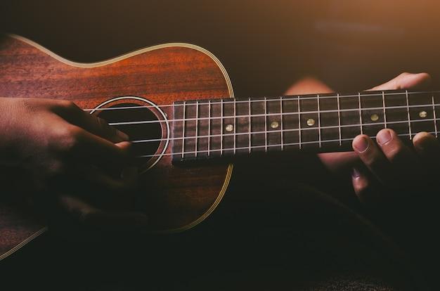 Ręce, Grając Na Akustycznej Gitarze Ukulele. Pokaż Umiejętności Muzyczne Premium Zdjęcia