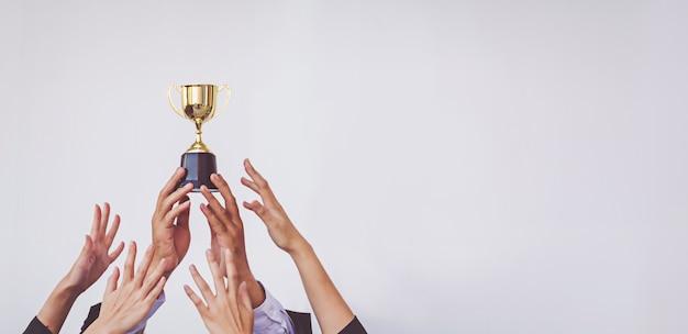 Ręce Gramolą Się O Złoty Puchar Trofeum, Biznes Koncepcyjny Premium Zdjęcia
