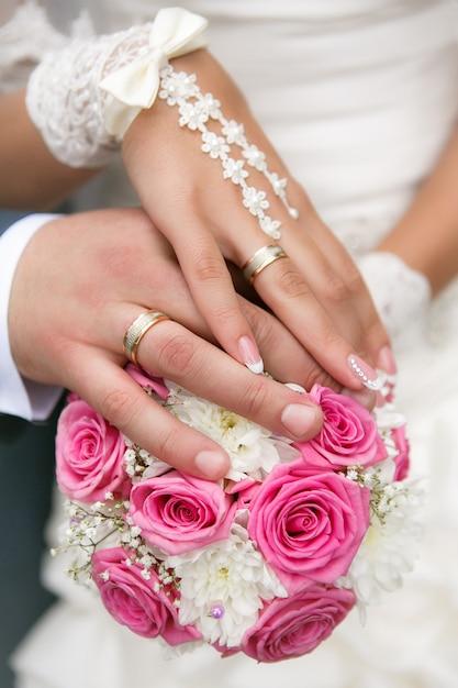 Ręce i pierścienie na bukiet ślubny Premium Zdjęcia
