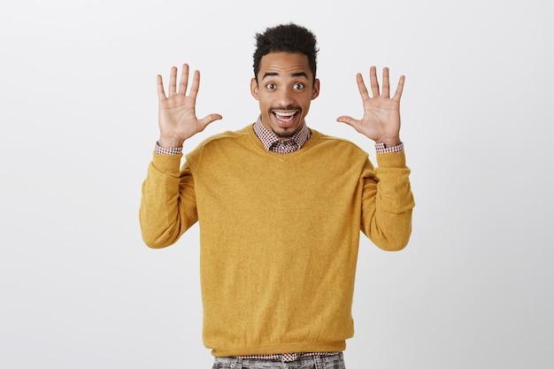 Ręce Jazzowe Zawsze W Modzie. Portret Szczęśliwego, Emocjonalnego Młodego Mężczyzny Z Fryzurą W Stylu Afro, Unoszącym Dłonie I Szeroko Uśmiechającym Się, Poddającym Się Lub Wyrażającym życzliwość I Dobry Nastrój Darmowe Zdjęcia