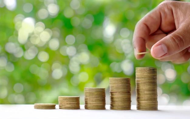 Ręce kładą monety nakładające się na zielony charakter. Premium Zdjęcia