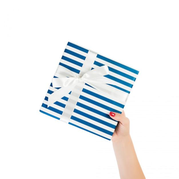 Ręce Kobiety Dają Owinięty Ręcznie świąteczny Lub Inny świąteczny Prezent W Niebieskim Papierze Z Białą Wstążką. Premium Zdjęcia