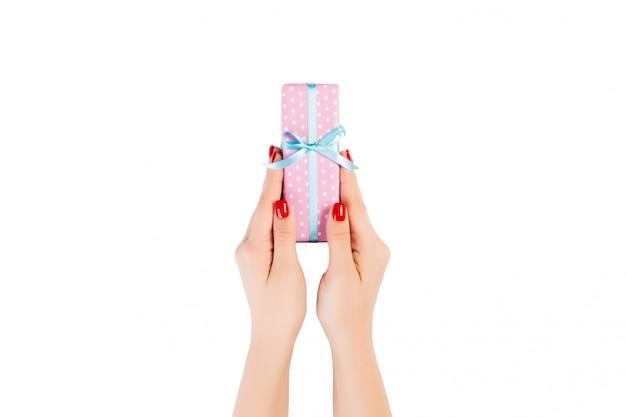 Ręce Kobiety Dają Owinięty Ręcznie świąteczny Lub Inny świąteczny Prezent W Różowym Papierze Z Niebieską Wstążką Premium Zdjęcia