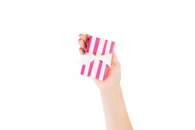 Ręce Kobiety Dają Owinięty świąteczny Lub Inny świąteczny Ręcznie Robiony Prezent W Różowej Papierowej Białej Wstążce. Pojedynczo Na Białym, Widok Z Góry. Pudełko Na święto Dziękczynienia Premium Zdjęcia