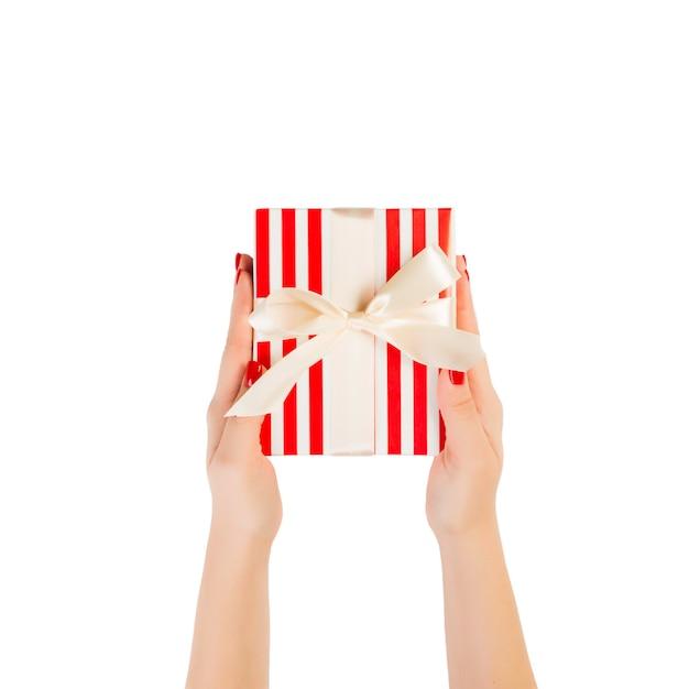 Ręce Kobiety Dają Zapakowane Prezenty świąteczne Lub Inne Ręcznie Robione W Czerwonym Papierze Ze Złotą Wstążką. Premium Zdjęcia